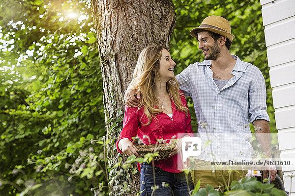 Junges Paar mit Blumenkorb im Garten