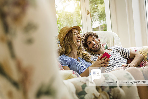 Junges Paar beim Lesen von Nachrichten auf dem Smartphone im Wohnzimmer