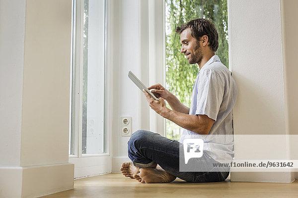 Mittlerer Erwachsener Mann mit Touchscreen auf digitalem Tablett im Wohnzimmer