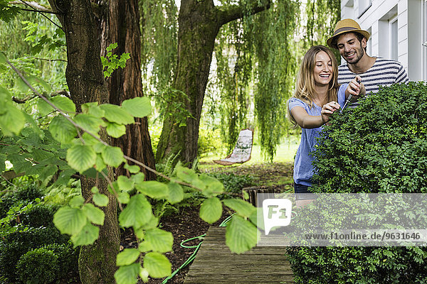 Junges Paar im Gartenstrauch