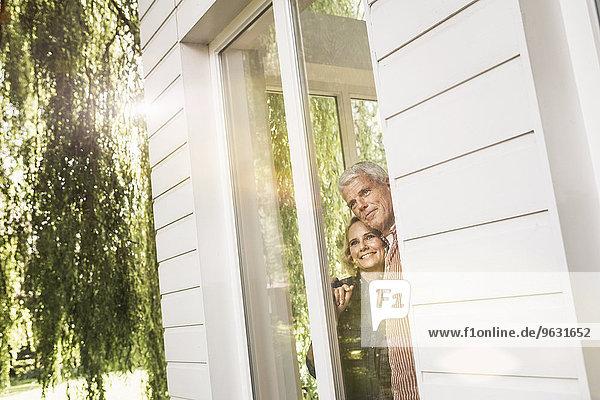 Ehemann und Ehefrau schauen aus dem Fenster in den Garten