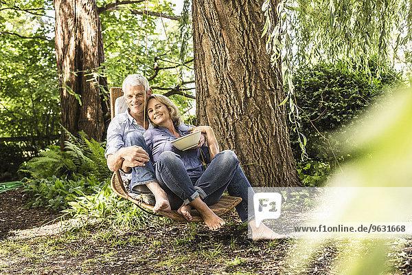 Mann und Frau beim Entspannen mit Kirschenschale auf der Hängematte