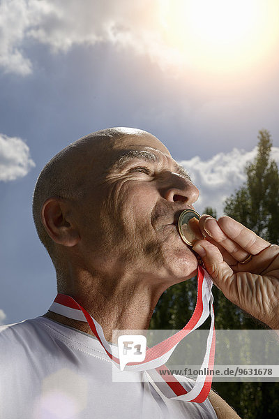 Sportsman kissing medal