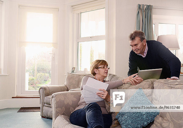 Seniorenpaar zu Hause mit Blick auf Dokumente und digitales Tablett