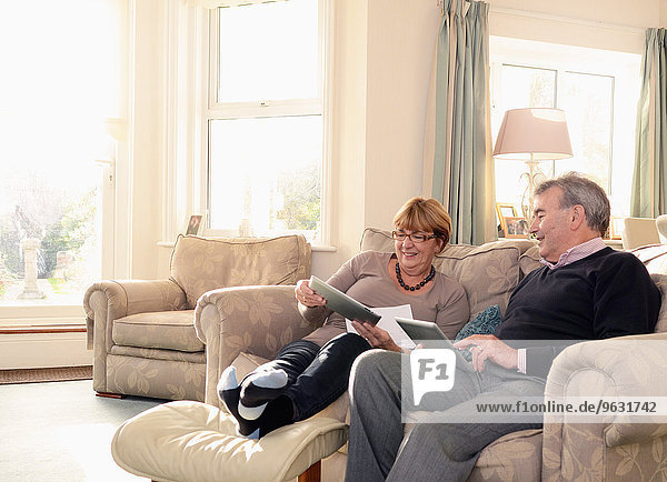 Senior couple at home on sofa  looking at digital tablets