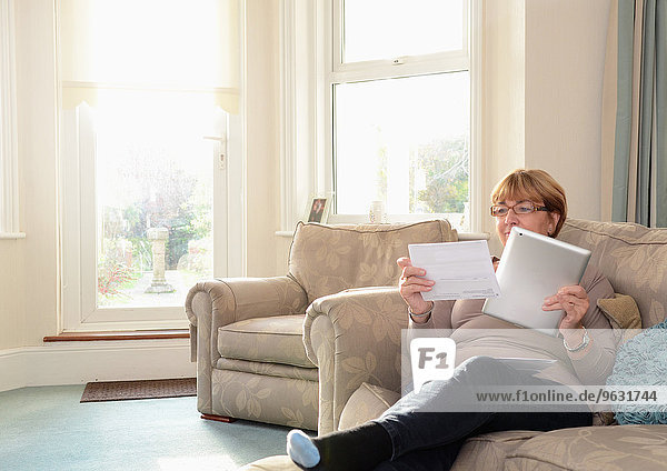 Senior woman sitting on sofa using digital tablet