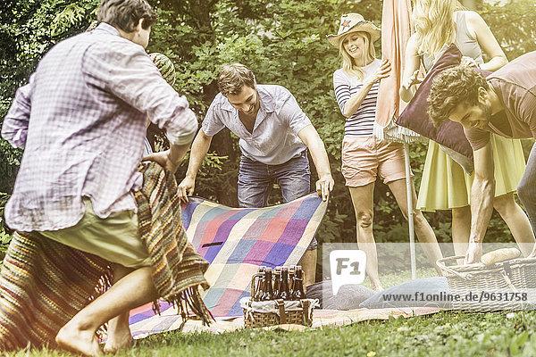 Freund bereitet sich auf ein Picknick im Garten vor