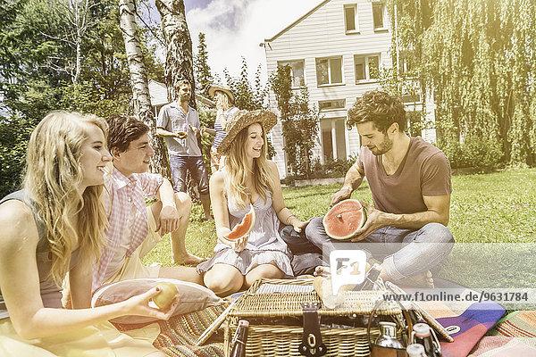Freunde beim Picknick im Garten  Mann beim Wassermelonenschneiden
