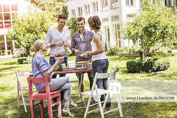 Gruppe von Freunden gründet Gartenparty