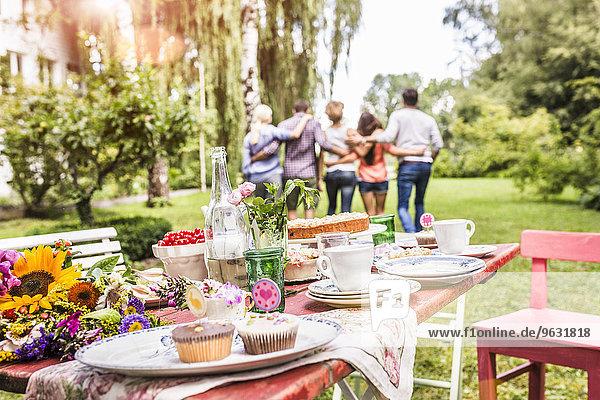 Gruppe von Freunden  die mit den Armen umeinander herum gehen  Gartenparty-Tisch mit Essen im Vordergrund