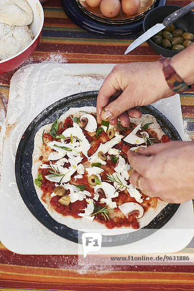 Female hands preparing pizza on garden table