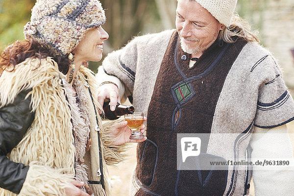 Ein reifes Hippie-Pärchen gießt ein Glas Apfelwein in den Garten.