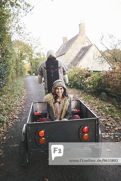 Rückansicht eines reifen Hippie-Paares mit Dreirad und Anhänger auf der Landstraße