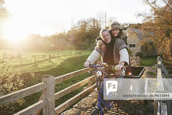 Altes Hippie-Paar auf Dreirad und Anhänger auf Landstraße