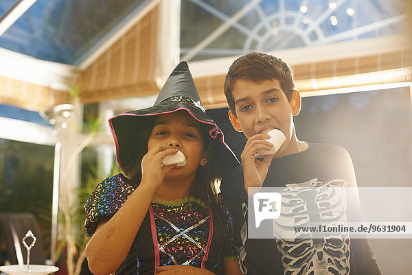Brother and sister wearing halloween costumes eating marshmallows