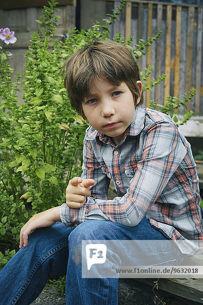 Portrait of boy pointing finger on allotment