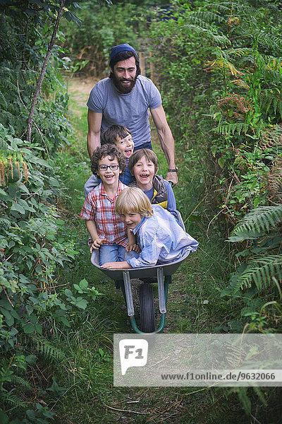 Mittlerer Erwachsener Mann schiebt Schubkarre mit lächelnden Jungen im Garten