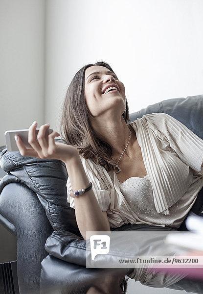 Junge Frau auf Sofa mit Smartphone  lachend