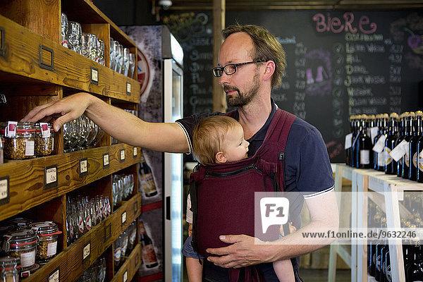 Vater mit kleiner Tochter beim Anblick von Gläsern im Laden