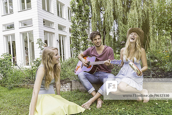 Drei Freunde im Garten  Mann spielt Gitarre