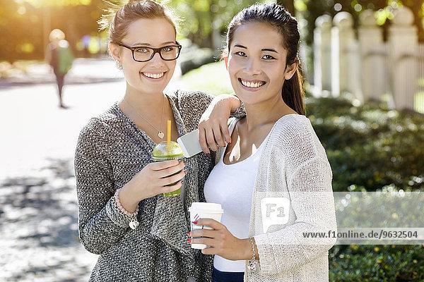 Porträt von zwei jungen Freundinnen im Park beim Kaffee zum Mitnehmen