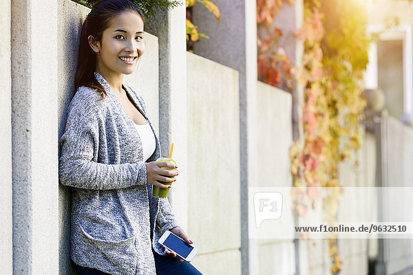 Portrait of young woman leaning against park wall drinking takeaway coffee