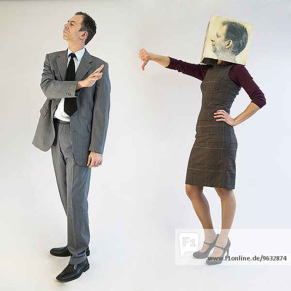 Businesswoman with mask showing thumbs down to businessman