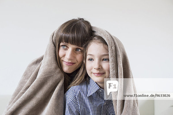 Mother and daughter covered with blanket  smiling