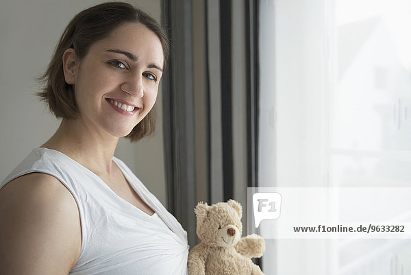 Portrait woman holding toy teddy bear close-up