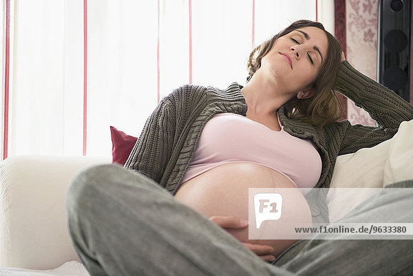 Pregnant young woman sofa lounge relaxing