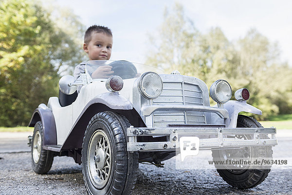 Small boy sitting driving model vintage car