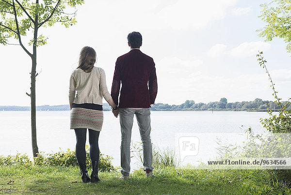 Rear view couple standing lake shore romantic