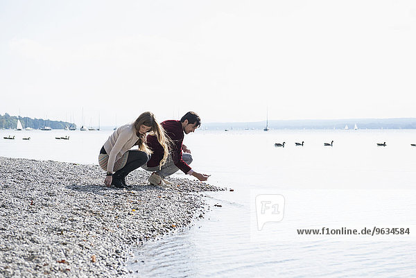 Young couple lake shore gathering pebbles