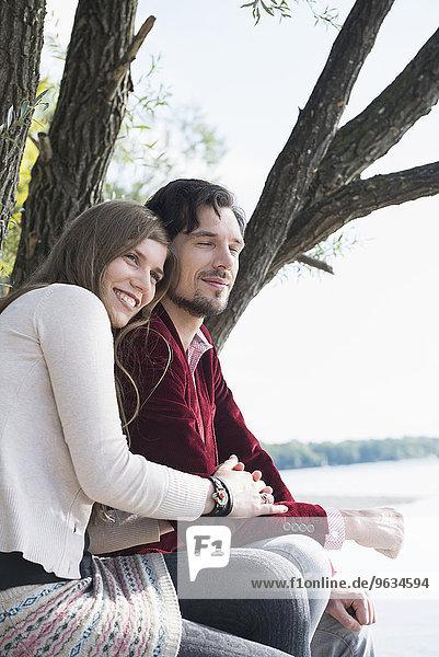 Happy young couple sitting lake