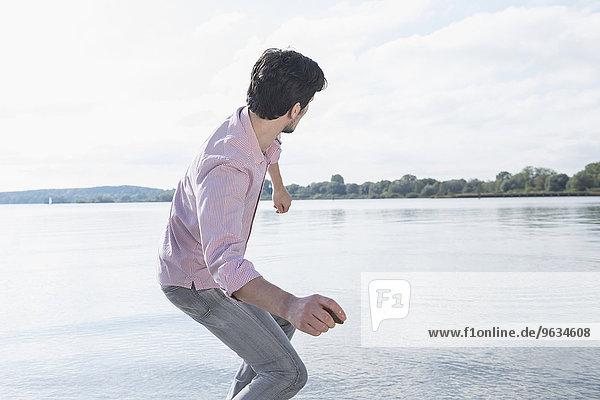 Man throwing stone water lake fun