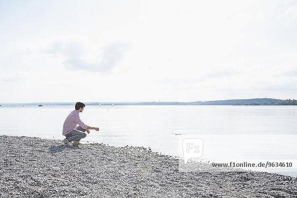 Man alone lake skimming stones