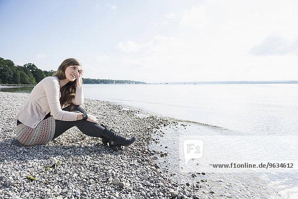 Pretty young woman sitting lake shore