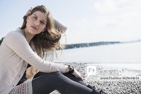 Portrait pretty young woman sitting lake shore
