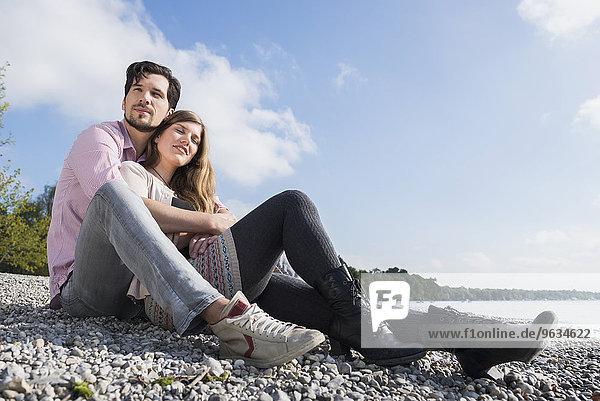 Couple sitting hugging lake shore happy