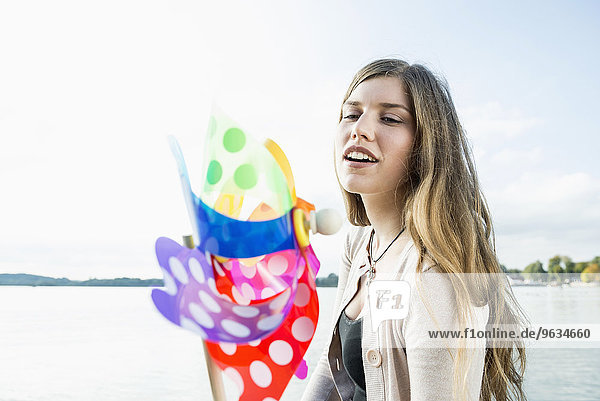 Young woman holding colourful toy windmill