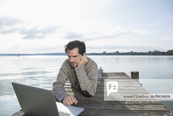 Young man lying on wooden jetty lake laptop