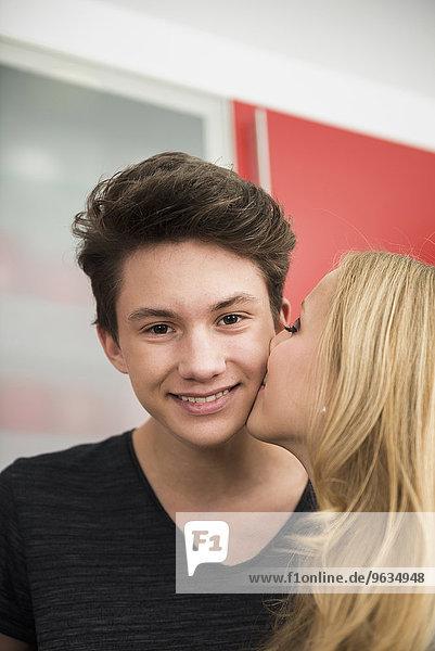 Young woman kissing man cheek