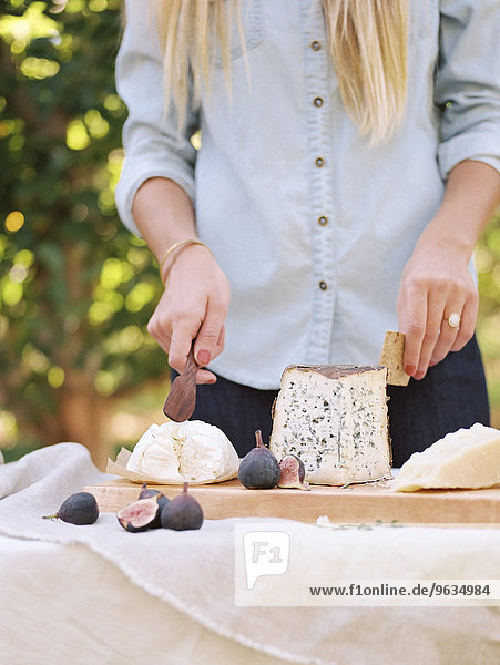 An apple orchard in Utah. Woman standing at a table with food  a cheese board.
