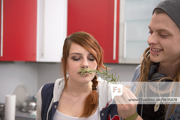 Woman smelling a twig of rosemary