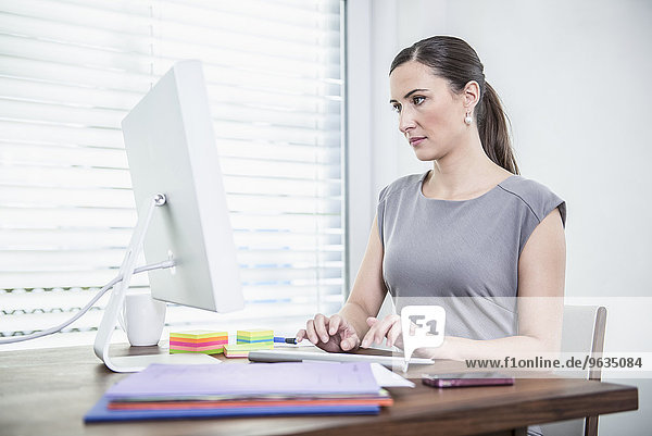 Businesswoman sitting at desk working on computer in office Businesswoman sitting at desk working on computer in office