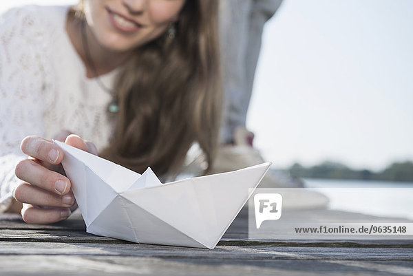 Close up woman holding white paper boat detail
