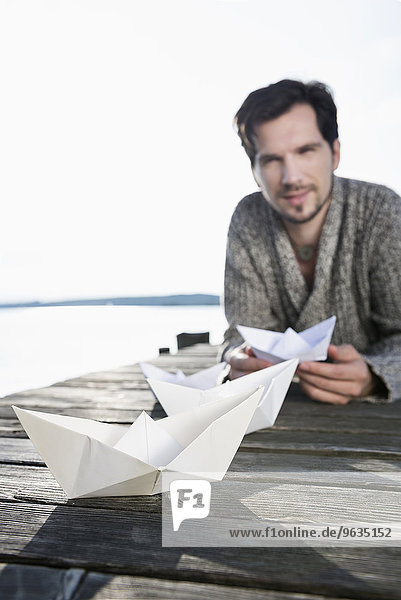Paper boat man building wooden jetty lake