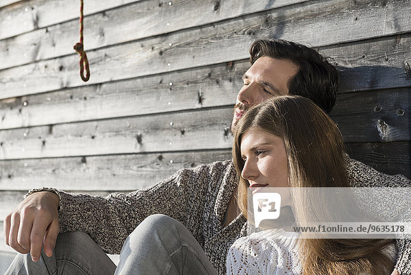 Couple man woman relaxing wooden wall