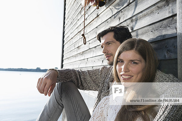 Young couple sitting boathouse wall portrait