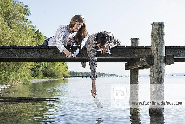 Young man woman launching paper boat jetty